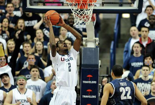 Connecticut's DeAndre Daniels lines up a dunk as Georgetown's Otto Porter Jr. (22) watches during the first half of an NCAA college basketball game in Storrs, Conn., Wednesday, Feb. 27, 2013. (AP Photo/Jessica Hill) Photo: Jessica Hill, Associated Press / FR125654 AP