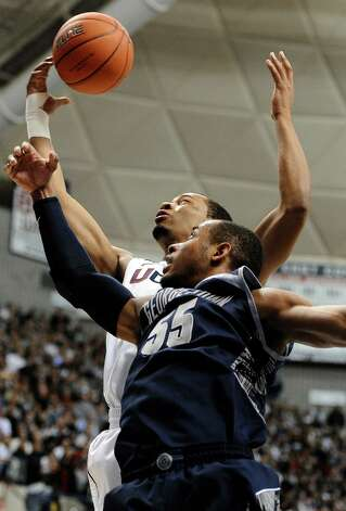 Connecticut's Omar Calhoun, back pulls down a defensive rebound against Georgetown's Jabril Trawick during the first half of an NCAA college basketball game in Storrs, Conn., Wednesday, Feb. 27, 2013. (AP Photo/Jessica Hill) Photo: Jessica Hill, Associated Press / FR125654 AP