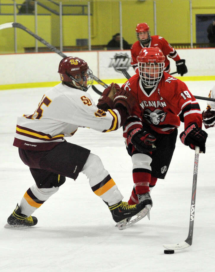 New Canaan's Henry Stanton, right, fends off St. Joseph's Ryan Corcoran during their FCIAC semifinal game at Terry Conners Rink in Stamford on Wednesday, Feb. 27, 2013. Photo: Jason Rearick / The Advocate