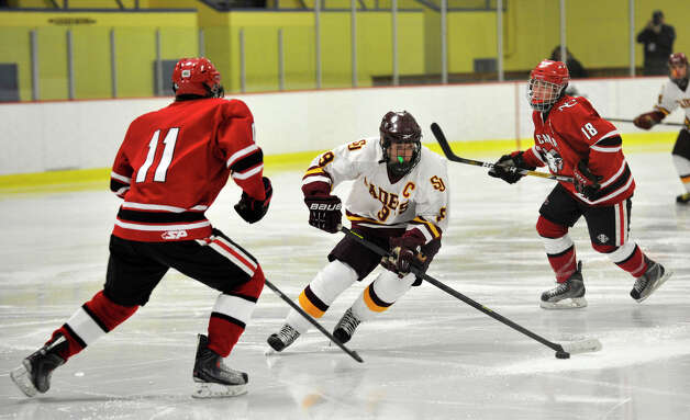 St. Joseph's Christian Keator, center, evades New Canaan defender John O'Rourke during their FCIAC semifinal game at Terry Conners Rink in Stamford on Wednesday, Feb. 27, 2013. Photo: Jason Rearick / The Advocate