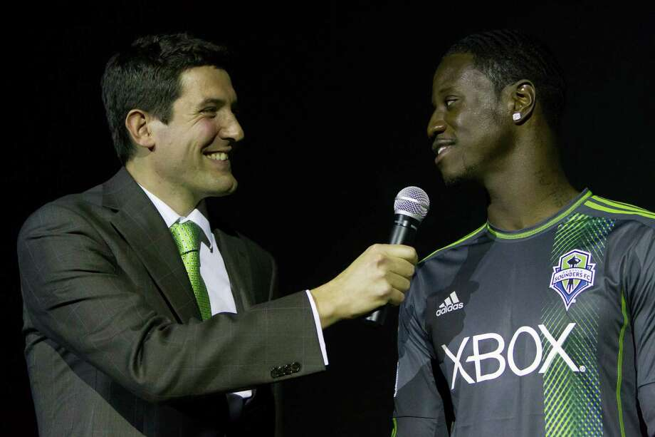 Announcer Ross Fletcher, left, addresses Sounders FC player Eddie Johnson at the unveiling event for the new 2013 season uniforms of the Seattle Sounders FC on Wednesday, Feb. 27, 2013, at the Cinerama in downtown Seattle, Wash. Both outfits - primary, in green, and secondary, in slate - boasted reduced fabric weights and a change in some stitching materials. Photo: JORDAN STEAD / SEATTLEPI.COM