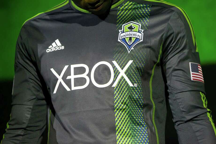 Eddie Johnson observes the details of the new secondary uniforms of the Seattle Sounders FC on Wednesday, Feb. 27, 2013, at the Cinerama in downtown Seattle, Wash. Both outfits - primary and secondary - boasted reduced fabric weights and a change in some stitching materials. Photo: JORDAN STEAD / SEATTLEPI.COM