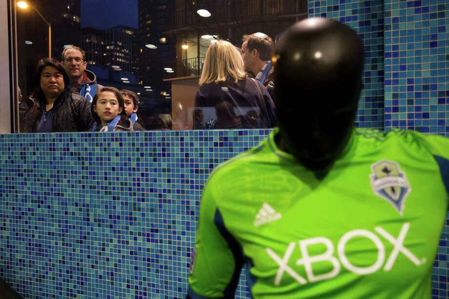 Sounders FC fans peek in at the unveiling event for the new uniforms of the Seattle Sounders FC on Wednesday, Feb. 27, 2013, at the Cinerama in downtown Seattle, Wash. Both outfits - primary and secondary - boasted reduced fabric weights and a change in some stitching materials. Photo: JORDAN STEAD / SEATTLEPI.COM