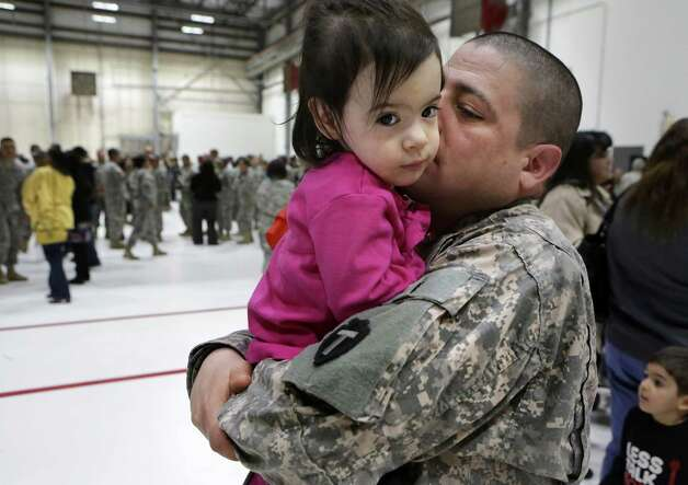 Sgt. Jason De Leon hugs his daughter Bianca De Leon, 2 yrs, as members of the 449th Aviation Support Battalion of the Army National Guard participate in a mobilization ceremony at the Austin Army Aviation Support Facility on Wednesday, Feb. 27, 2013. The group is being deployed to Kuwait. Photo: Bob Owen, San Antonio Express-News / ©2013 San Antonio Express-News