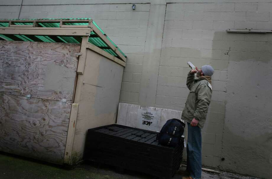 A man chugs a bottle of fortified wine behind the Lake City Grocery Outlet. The store is struggling because of a significant increase in theft. The  increase is blamed on Seattle's plastic bag ban and a concentration of  inebriates and drug users in the neighborhood. Nearby Fred Meyer also  suffers from the highest theft rate in the entire chain, members of the North Seattle Chamber of Commerce were told. A company  spokeswoman said that's incorrect, but did not say which location did  have the highest theft. Photo: JOSHUA TRUJILLO / SEATTLEPI.COM
