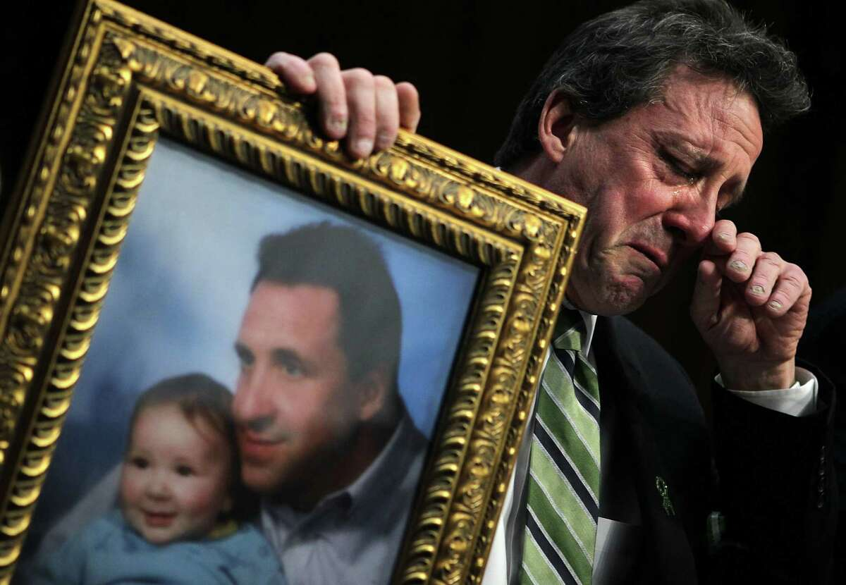 """WASHINGTON, DC - FEBRUARY 27: Neil Heslin, father of six-year-old Sandy Hook Elementary School shooting victim Jesse Lewis, holds a picture of him with Jesse as he testifies during a hearing before the Senate Judiciary Committee February 27, 2013 on Capitol Hill in Washington, DC. The committee held a hearing on """"The Assault Weapons Ban of 2013."""" (Photo by Alex Wong/Getty Images)"""