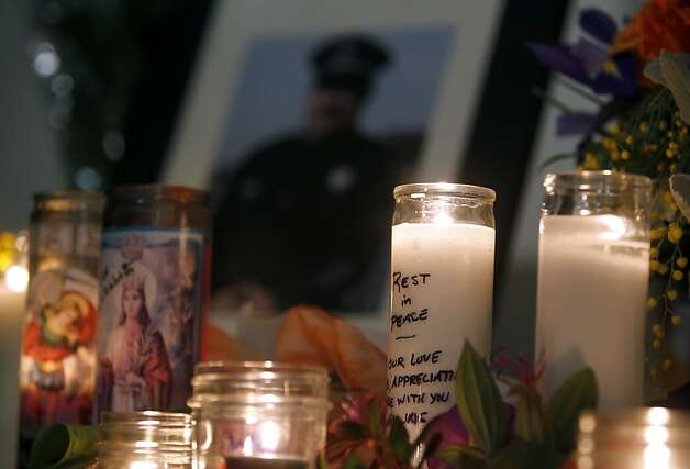"Candles and flowers commemorate Detective Sgt. Loran ""Butch"" Baker and Detective Elizabeth Butler at a community vigil in Santa Cruz the day after they were gunned down. Photo: Paul Chinn, The Chronicle"