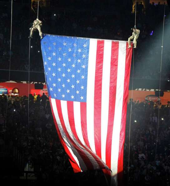The U.S. Air Force rappelling team lowers a U.S. flag before Alan Jackson performs for Rodeo Houston
