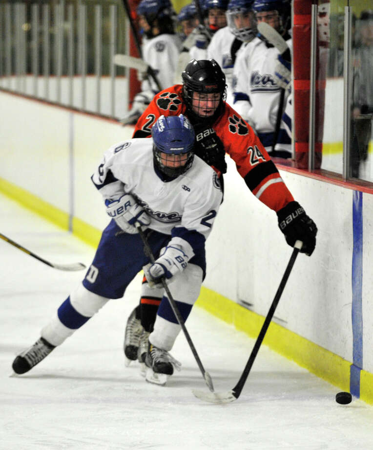 Ridgefield's Christian O'Connell tries to reach over the back of Darien's Jack Pardue during their FCIAC semifinal game at Terry Conners Rink in Stamford on Wednesday, Feb. 27, 2013. Photo: Jason Rearick / The Advocate