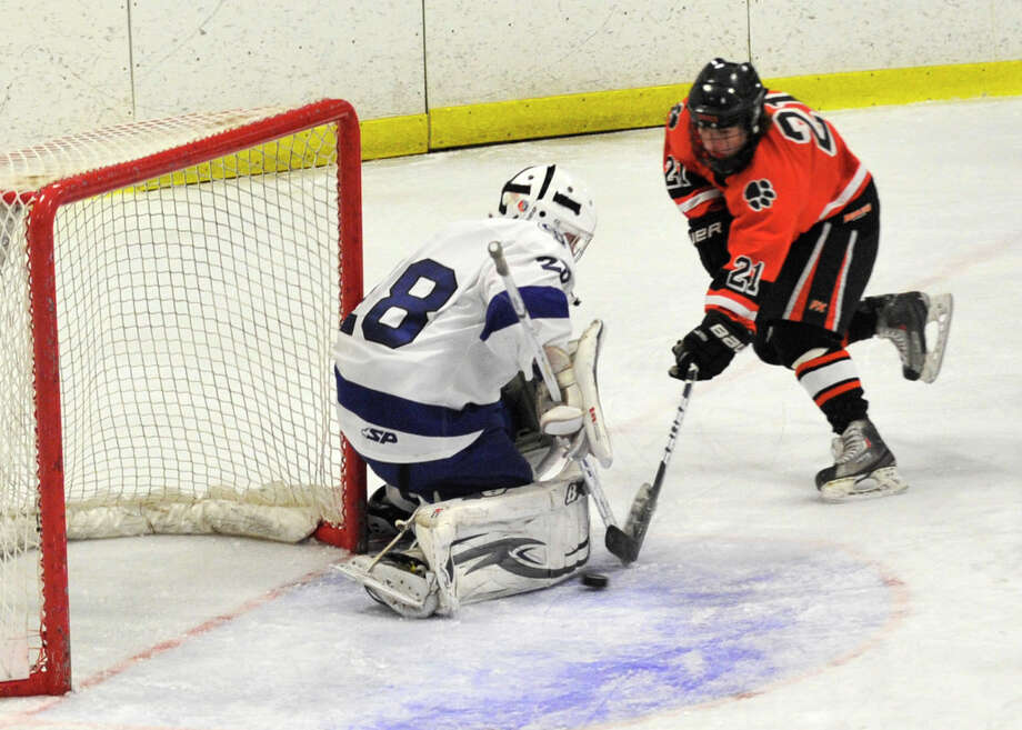 Ridgefield's Cameron McGuire shoots on Darien goalie Michael Collins during their FCIAC semifinal game at Terry Conners Rink in Stamford on Wednesday, Feb. 27, 2013. Photo: Jason Rearick / The Advocate