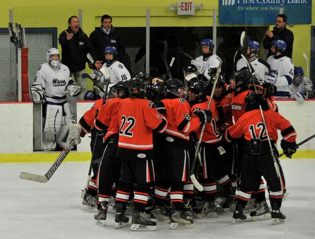 Ridgefield teammates celebrate in front of the Darien bench after defeating them in overtime in the FCIAC semifinal game at Terry Conners Rink in Stamford on Wednesday, Feb. 27, 2013. Photo: Jason Rearick / The Advocate