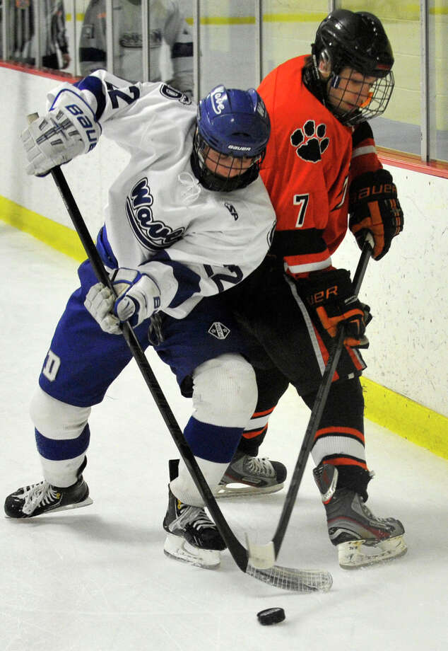 Darien's Jack Pardue keeps the puck from Ridgefield's Chris Morrow during their FCIAC semifinal game at Terry Conners Rink in Stamford on Wednesday, Feb. 27, 2013. Photo: Jason Rearick / The Advocate