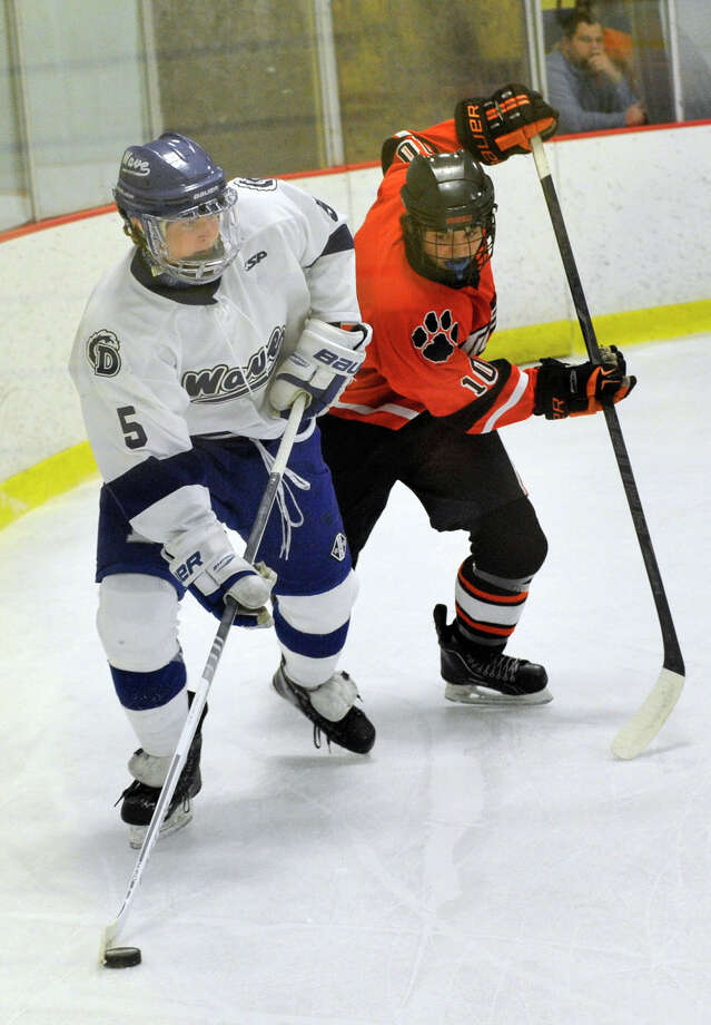 Darien's Owen Koorbusch looks for an open man while under pressure from Ridgefield's Shane Luery during their FCIAC semifinal game at Terry Conners Rink in Stamford on Wednesday, Feb. 27, 2013. Photo: Jason Rearick / The Advocate