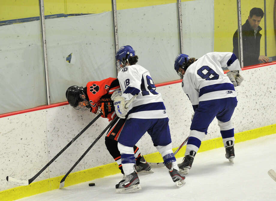 Ridgefield's Chris Morrow is ambushed by Darien's Kevin Love, center, and Dana Wensberg during their FCIAC semifinal game at Terry Conners Rink in Stamford on Wednesday, Feb. 27, 2013. Photo: Jason Rearick / The Advocate