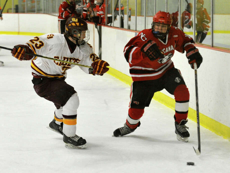 St. Joseph's Sean Smith challenges New Canaan's Parker Lewis during their FCIAC semifinal game at Terry Conners Rink in Stamford on Wednesday, Feb. 27, 2013. Photo: Jason Rearick / The Advocate