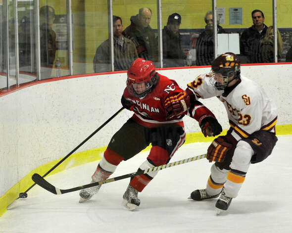 New Canaan's Luke Amero keeps the puck away from St. Joseph's Sean Smith during their FCIAC semifinal game at Terry Conners Rink in Stamford on Wednesday, Feb. 27, 2013. Photo: Jason Rearick / The Advocate