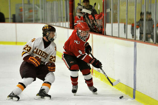 St. Joseph's Sean Smith prepares to hit New Canaan's Henry Stanton during their FCIAC semifinal game at Terry Conners Rink in Stamford on Wednesday, Feb. 27, 2013. Photo: Jason Rearick / The Advocate