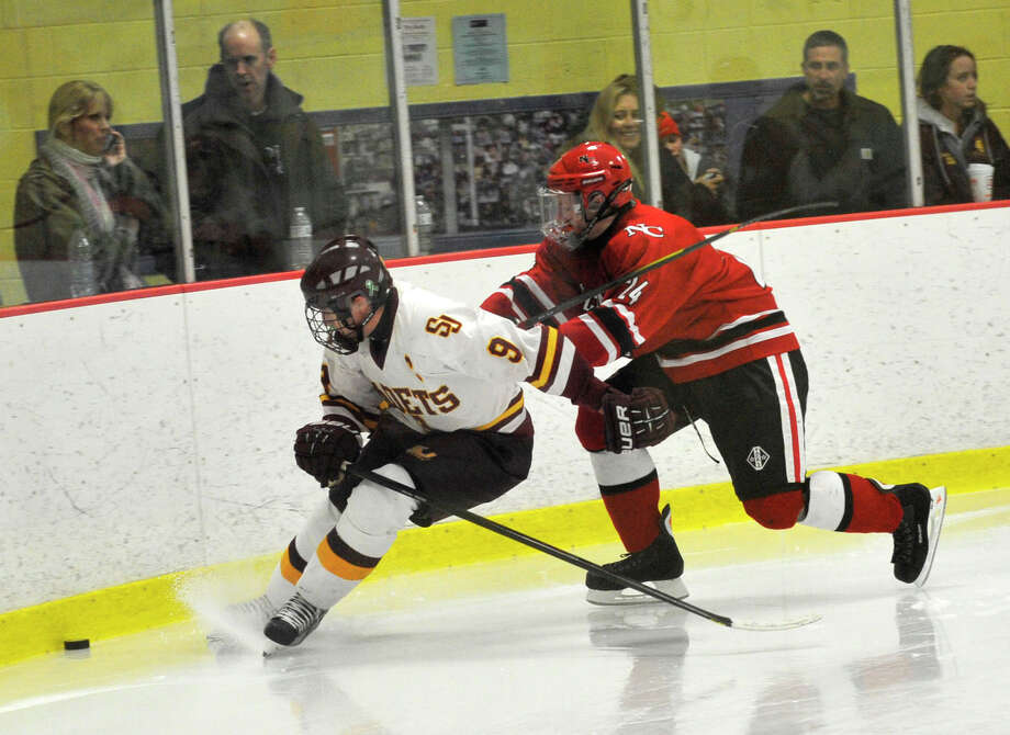 St. Joseph's Christian Keator keeps the puck from New Canaan's Trent Nader during their FCIAC semifinal game at Terry Conners Rink in Stamford on Wednesday, Feb. 27, 2013. Photo: Jason Rearick / The Advocate