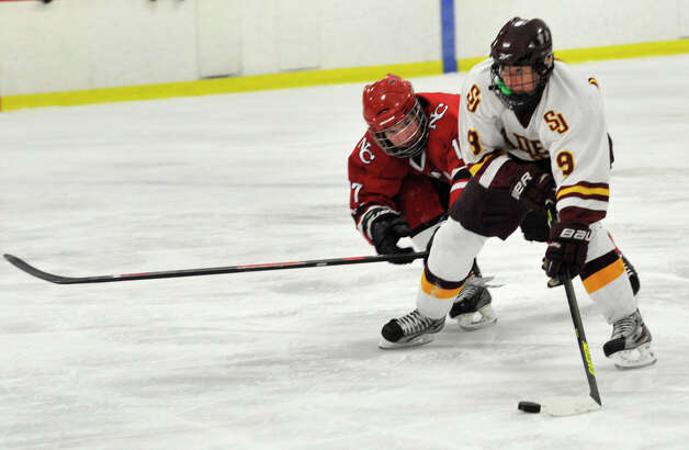 St. Joseph's Christian Keator is challenged by New Canaan's Stephen Mettler during their FCIAC semifinal game at Terry Conners Rink in Stamford on Wednesday, Feb. 27, 2013. Photo: Jason Rearick / The Advocate
