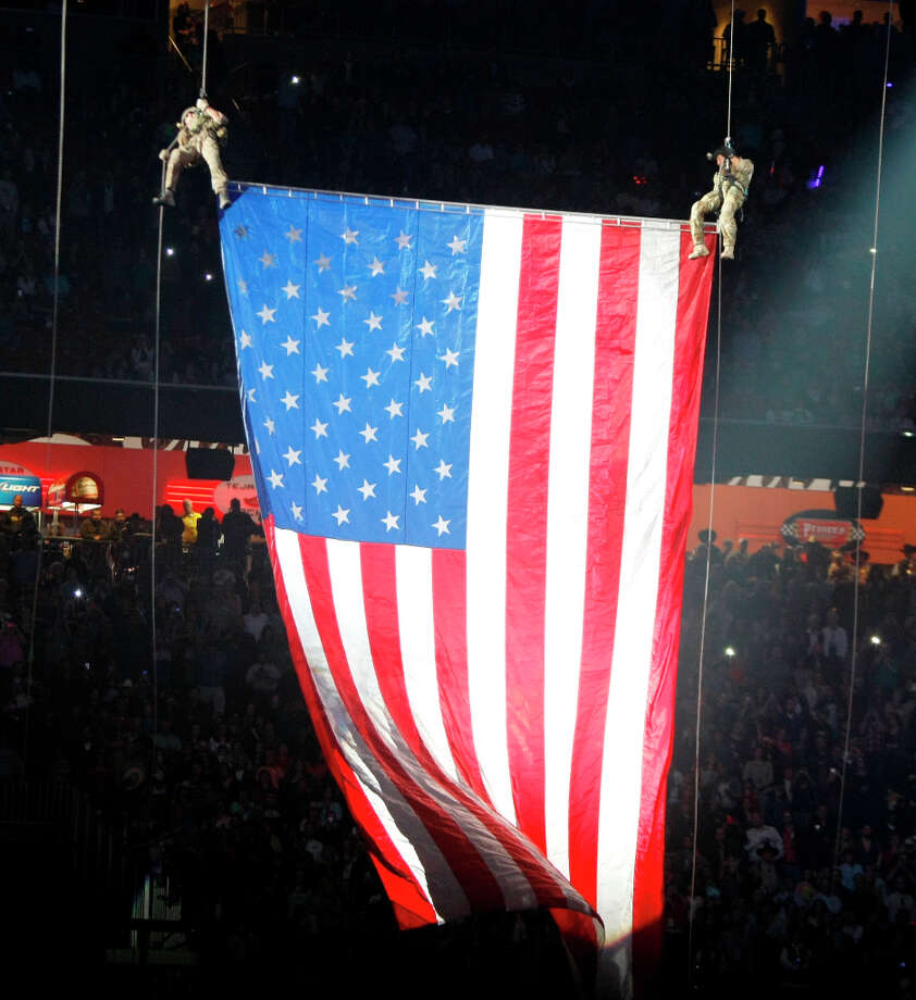 The U.S. Air Force repel team lowers a U.S. flag before Alan Jackson performs on Feb. 27. Photo: Nick De La Torre, Chronicle / © 2013 Houston Chronicle