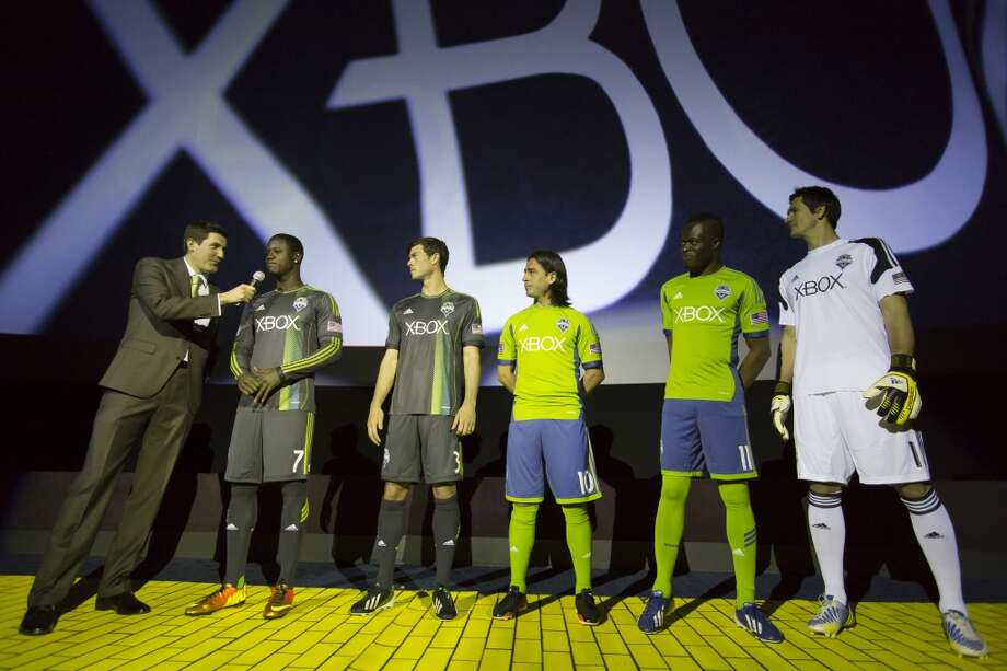 Announcer Ross Fletcher, left, addresses Sounders FC players (from left) Eddie Johnson, Brad Evans, Mauro Rosales, Steve Zakuani and Michael Gspurning at the unveiling event for the new 2013 season uniforms of the Seattle Sounders FC on Wednesday, Feb. 27, 2013, at the Cinerama in downtown Seattle. Both outfits - primary, in green, and secondary, in slate - boasted reduced fabric weights and a change in some stitching materials.