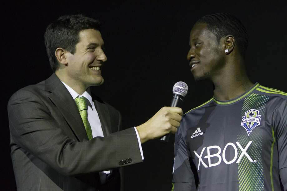 Announcer Ross Fletcher, left, addresses Sounders FC player Eddie Johnson at the unveiling event for the new 2013 season uniforms of the Seattle Sounders FC on Wednesday, Feb. 27, 2013, at the Cinerama in downtown Seattle, Wash. Both outfits - primary, in green, and secondary, in slate - boasted reduced fabric weights and a change in some stitching materials.