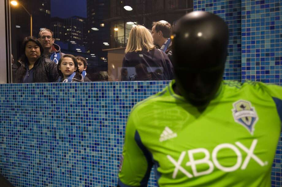 Sounders FC fans peek in at the unveiling event for the new uniforms of the Seattle Sounders FC.