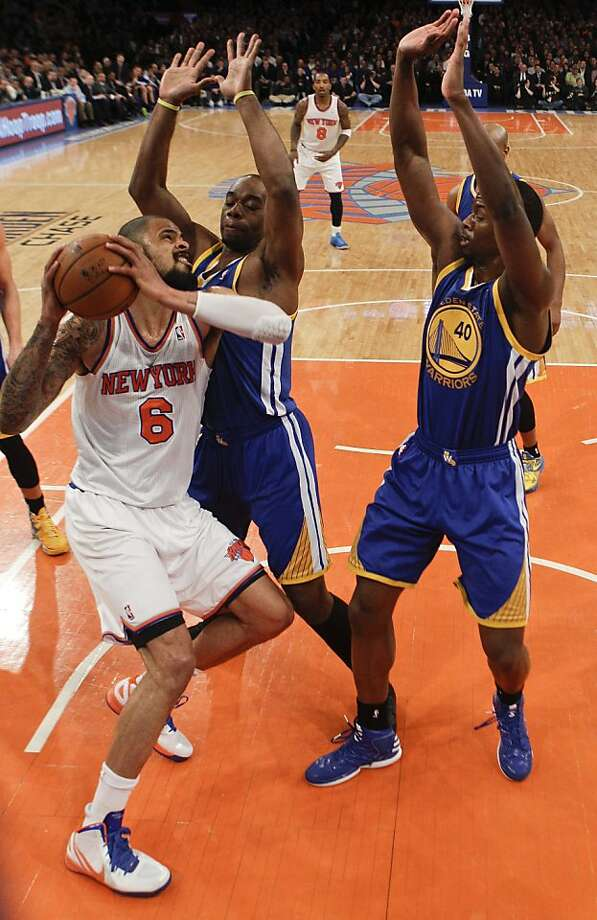 New York Knicks' Tyson Chandler (6) protects the ball from Golden State Warriors' Carl Landry, center, and Harrison Barnes, right, during the first half of an NBA basketball game on Wednesday, Feb. 27, 2013, in New York. Chandler had 28 rebounds as the Knicks won the game 109-105. (AP Photo/Frank Franklin II) Photo: Frank Franklin II, Associated Press