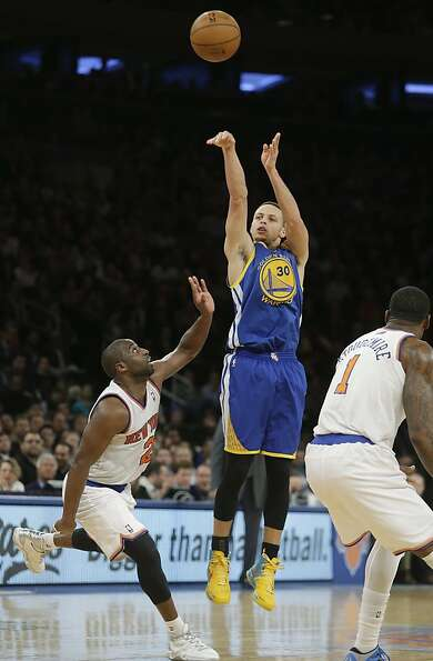 Golden State Warriors' Stephen Curry, center, shoots over New York Knicks' Raymond Felton, left, and