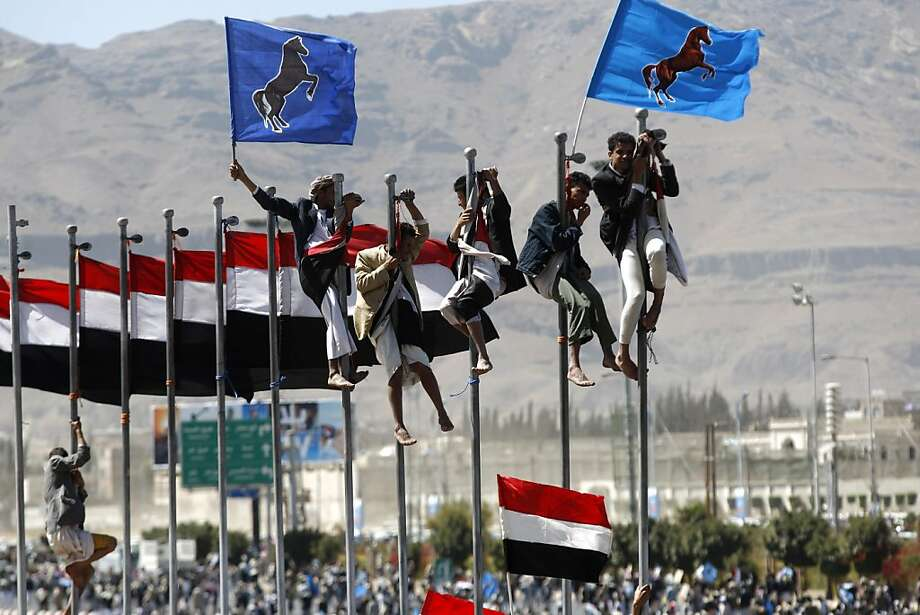 Supporters of Yemen's former President Ali Abdullah Saleh climb on flag poles during a rally marking the anniversary of his power handover in Sanaa, Yemen, Wednesday, Feb. 27, 2013. Photo: Hani Mohammed, Associated Press