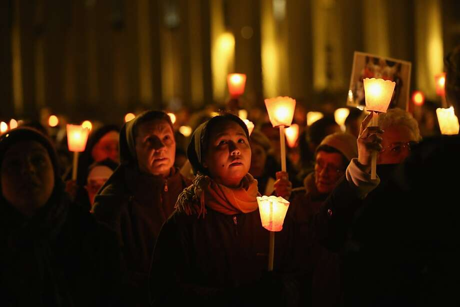 Pilgrims and clergy members hold a candle-lit vigil in Saint Peter's Square, facing Pope Benedict XVI's private apartment, after his final weekly public audience on February 27, 2013 in Vatican City, Vatican. The Pontiff has attended his last weekly public audience before stepping down tomorrow. Pope Benedict XVI has been the leader of the Catholic Church for eight years and is the first Pope to retire since 1415. He cites ailing health as his reason for retirement and will spend the rest of his life in solitude away from public engagements. Photo: Oli Scarff, Getty Images