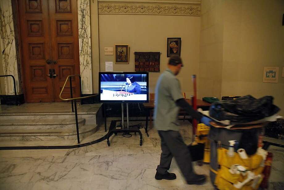 A City Hall custodian walks past a television set up for overflow viewing outside council chambers as Oakland Mayor Jean Quan gave the state of the city speech at City Hall in Oakland, Calif., on Wednesday, February 27, 2013. Photo: Carlos Avila Gonzalez, The Chronicle