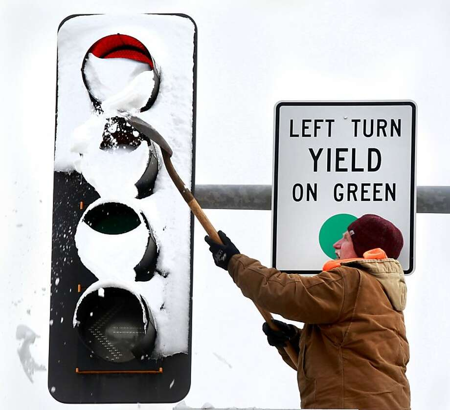 A Leawood Public Works crew worker clears snow from a north-facing traffic signal at 127th Street and Roe Avenue in Kansas City, Mo., Wednesday, Feb. 27, 2013. (AP Photo/The Kansas City Star, Fred Blocher) Photo: Fred Blocher, Associated Press