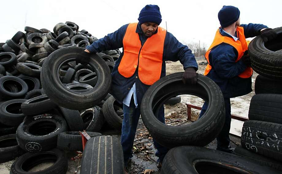 Shelby County inmates unload tires during the opening day of the city of Memphis' Tire Redemption program Wednesday, Feb. 27, 2013. A line more than a half mile long remained after the closed for the day many of whom will stay overnight to wait for it to reopen and stake their claim $1 per tire they collect.  The city is paying $1 per tire as a way of cleaning up the illegally dumped tires around the city. (AP Photo/The Commercial Appeal, Mike Brown) Photo: Mike Brown, Associated Press