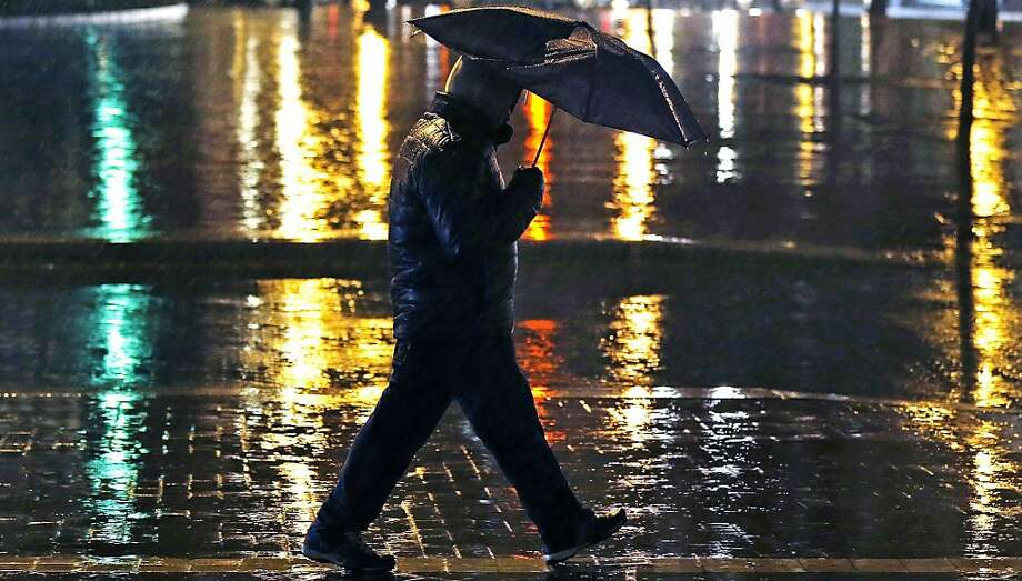 A man walks through the Financial District of Boston in a downpour during the evening commute in Boston, Wednesday, Feb. 27, 2013. (AP Photo/Charles Krupa) Photo: Charles Krupa, Associated Press