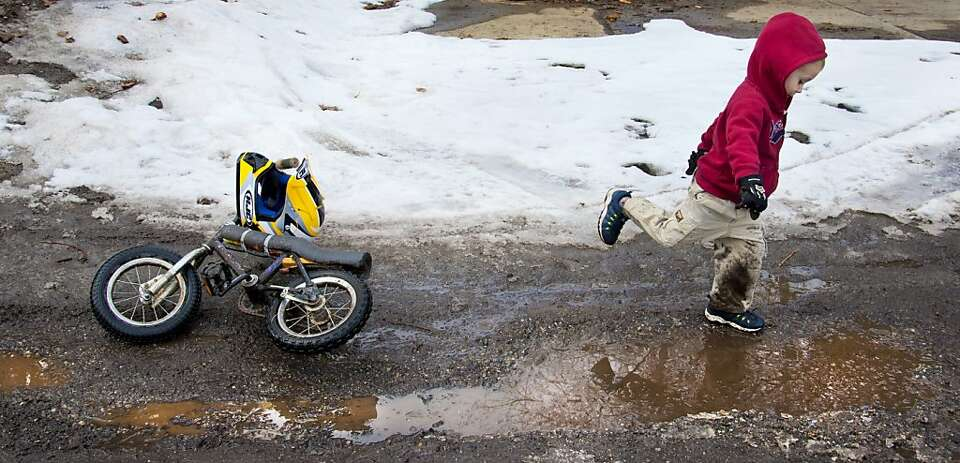 Whether to ride his mountain bike or splash in an icy mud puddle.  Miles McQuestern, 3, spent part o