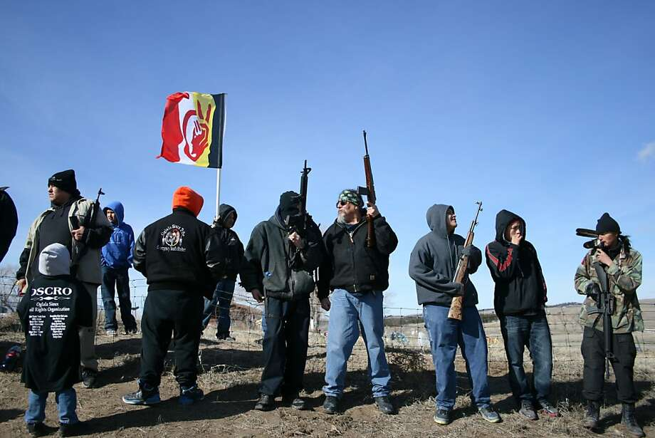 Members of the American Indian Movement stand near the Wounded Knee Massacre Monument, Wednesday, Feb. 27, 2013 in Wounded Knee, S.D. Wednesday marked the 40th anniversary of the start of the 71-day occupation in the village of Wounded Knee on the Pine Ridge Indian Reservation. Hundreds of AIM members and other supporters turned out for a day of ceremonies to commemorate the anniversary of the fatal standoff that drew national attention to the impoverished reservation and the plight of local tribes. (AP Photo/Kristi Eaton) Photo: Kristi Eaton, Associated Press