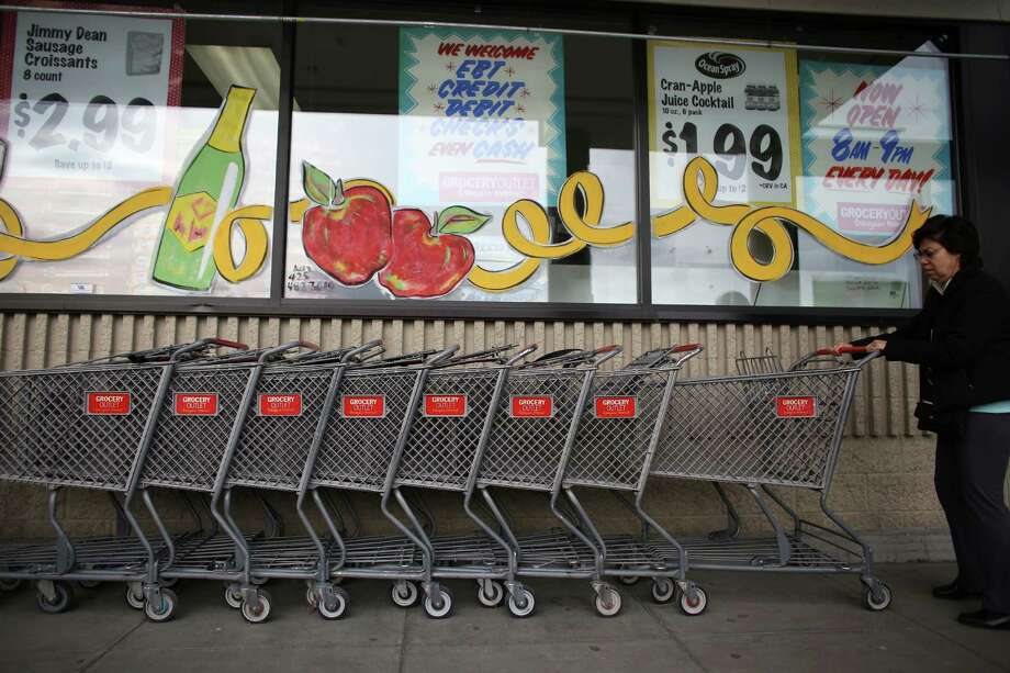 A customer prepares to shop at the Lake City Grocery Outlet. The store is struggling because of a significant increase in theft. The 