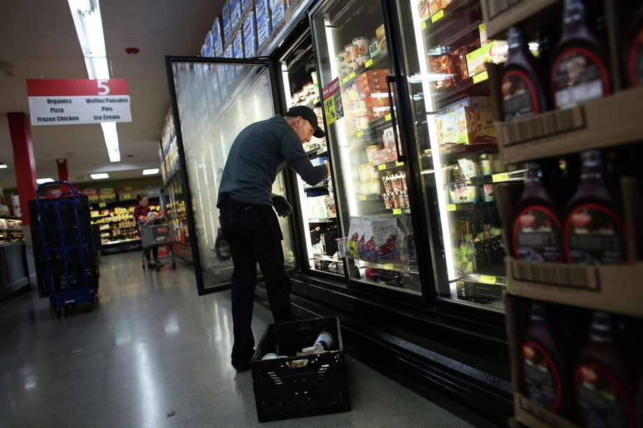 "Pablo Temeyosa stocks frozen items at the Lake City Grocery Outlet. The store has seen a significant increase in the theft of frozen items and produce since Seattle's plastic bag ban went into effect. Frozen items and produce aren't traditionally something that shoplifters ""would put down their pants,"" said an employee.  Photo: JOSHUA TRUJILLO / SEATTLEPI.COM"
