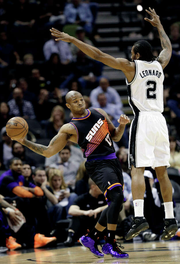 Phoenix Suns' P.J. Tucker (17) passes around San Antonio Spurs' Kawhi Leonard (2) during the first half of an NBA basketball game, Wednesday, Feb. 27, 2013, in San Antonio. Photo: Eric Gay, Associated Press / AP