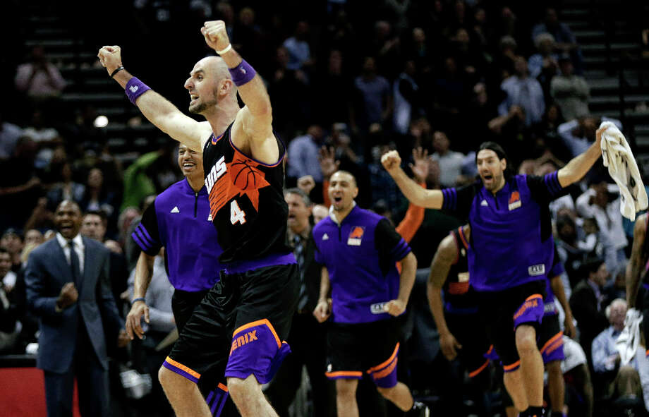 Phoenix Suns' Marcin Gortat (4), of Poland, and teammates celebrate a basket by Wesley Johnson at the buzzer to send the game into overtime during an NBA basketball game against the San Antonio Spurs on Wednesday, Feb. 27, 2013, in San Antonio. The Suns won 105-101 in overtime. Photo: Eric Gay, Associated Press / AP