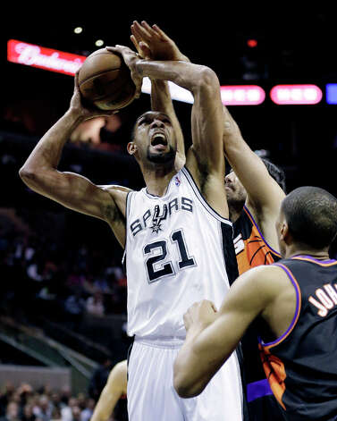 San Antonio Spurs' Tim Duncan (21) is fouled by Phoenix Suns' Luis Scola, rear, of Argentina, during the first half of an NBA basketball game, Wednesday, Feb. 27, 2013, in San Antonio. Suns' Wesley Johnson, right, also defends on the play. Photo: Eric Gay, Associated Press / AP
