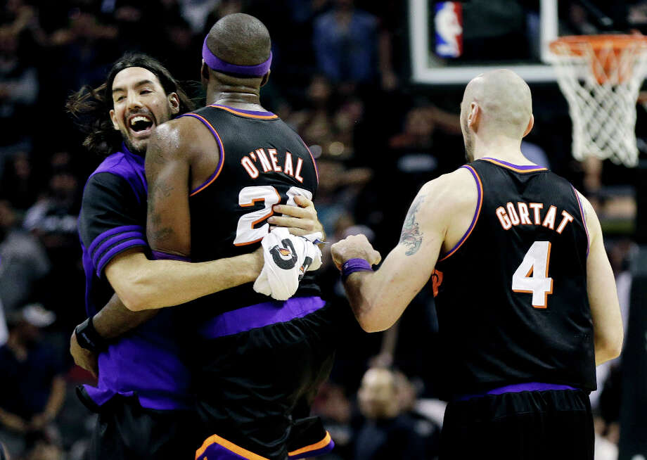 Phoenix Suns' Jermaine O'Neal (20) celebrates with teammates Luis Scola, left, and Marcin Gortat (4) after winning their NBA basketball game against the San Antonio Spurs, Wednesday, Feb. 27, 2013, in San Antonio. The Suns won 105-101 in overtime. Photo: Eric Gay, Associated Press / AP