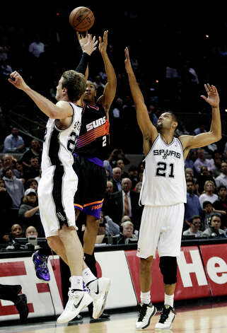 Phoenix Suns' Wesley Johnson (2) shoots a  basket over San Antonio Spurs' Tiago Splitter (22), of Brazil, and Tim Duncan (21) at the buzzer to send the game into overtime during the second half of an NBA basketball game, Wednesday, Feb. 27, 2013, in San Antonio. The Suns won 105-101 in overtime. Photo: Eric Gay, Associated Press / AP