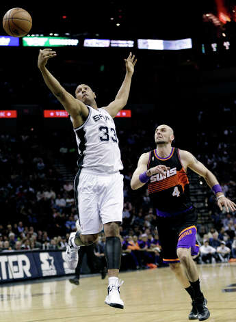 San Antonio Spurs' Boris Diaw (33), of France, leaps for a pass as Phoenix Suns' Marcin Gortat (4), of Poland, moves in to defend during the first half of an NBA basketball game, Wednesday, Feb. 27, 2013, in San Antonio. Photo: Eric Gay, Associated Press / AP