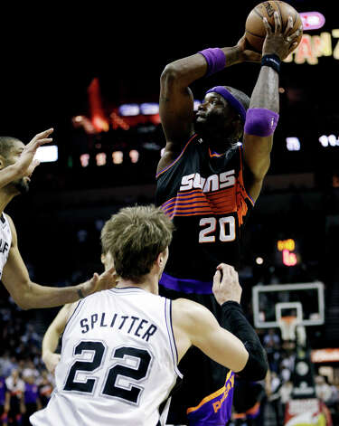 Phoenix Suns' Jermaine O'Neal (20) shoots over San Antonio Spurs' Tim Duncan, left, and Tiago Splitter (22) during overtime of an NBA basketball game, Wednesday, Feb. 27, 2013, in San Antonio. The Suns won 105-101. Photo: Eric Gay, Associated Press / AP