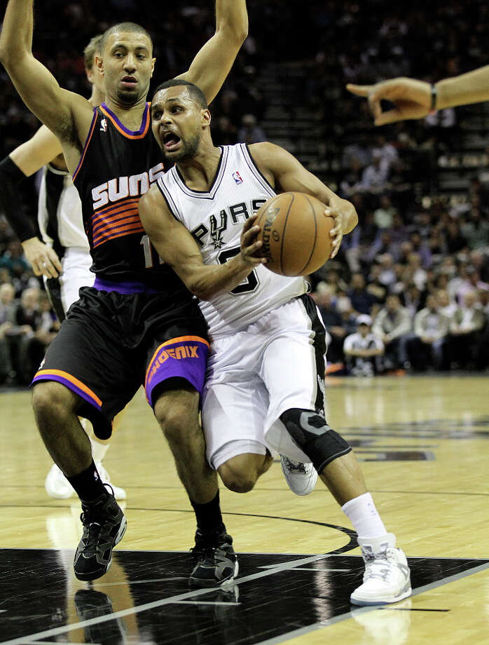 Spurs' Patty Mills (08) drives the lane against Phoenix Suns' Kendall Marshall (12) in the first half at the AT&T Center on Wednesday, Feb. 27, 2013. Photo: Kin Man Hui, San Antonio Express-News / © 2012 San Antonio Express-News