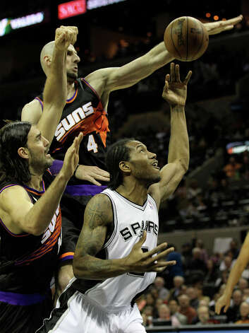 Spurs' Kawhi Leonard (02) gets blocked under the basket by Phoenix Suns' Marcin Gortat (04) and Luis Scola (14) in the second half at the AT&T Center on Wednesday, Feb. 27, 2013. Suns defeated the Spurs, 105-101. Photo: Kin Man Hui, San Antonio Express-News / © 2012 San Antonio Express-News