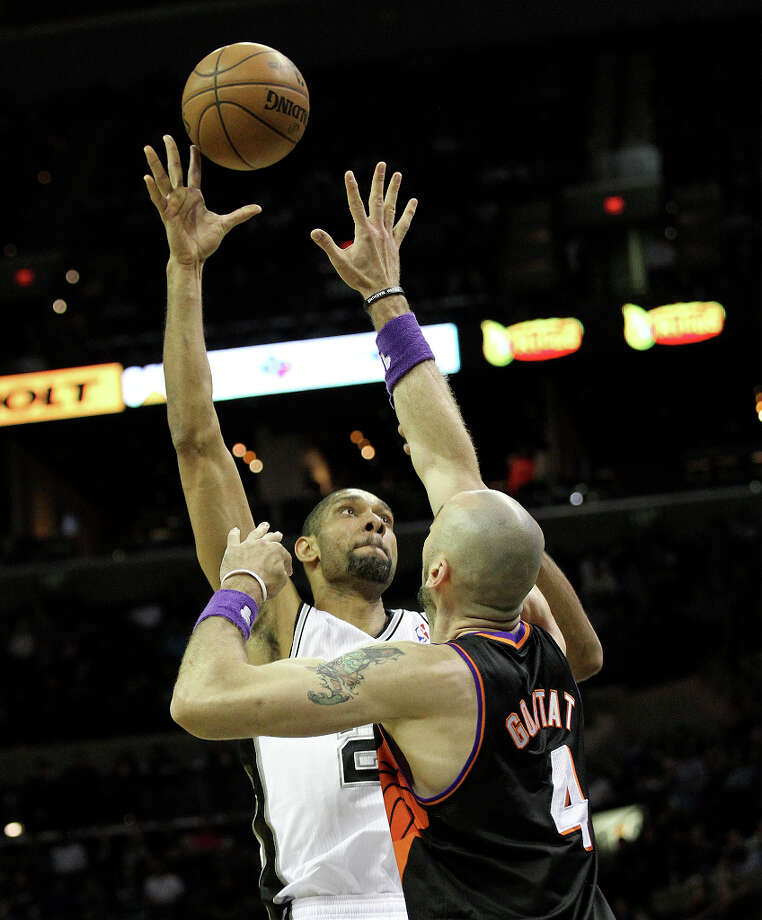 Spurs' Tim Duncan (21) attempts a shot over Phoenix Suns' Marcin Gortat (04) in the second half at the AT&T Center on Wednesday, Feb. 27, 2013. Suns defeated the Spurs, 105-101. Photo: Kin Man Hui, San Antonio Express-News / © 2012 San Antonio Express-News