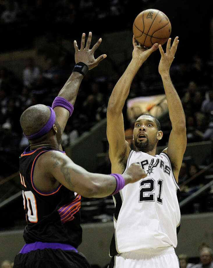 Spurs' Tim Duncan (21) attempts a shot over Phoenix Suns' Jermaine O'Neal (20) in the second half at the AT&T Center on Wednesday, Feb. 27, 2013. Suns defeated the Spurs, 105-101. Photo: Kin Man Hui, San Antonio Express-News / © 2012 San Antonio Express-News